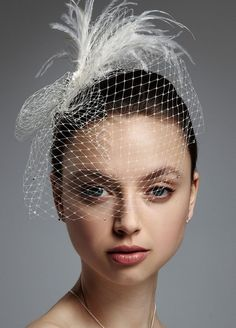 Feathered headpiece attached to Russian tulle (aka birdcage veil). More feather hair at http://tiaras.myonlineweddinghelp.com/feather-hair.htm