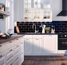 Love the navy subway tile with the white cabinets.