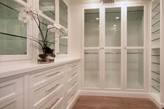 This walk-in closet features full length glass doors, glass shelving, and drawer storage.