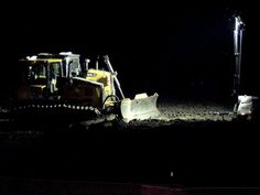 Bright lights illuminate a bulldozer at the site of construction of the Bakken oil pipeline after dark near Huxley during a recent moratorium on construction. Photo by Michael Crumb/Ames Tribune
