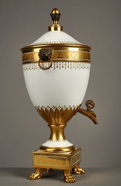 c1810 A French white and gilded porcelain fountain resting on a squared base with fours lions paws. Very finely decorated with gilded stylized foliage. Handles representing lions head holding a ring. Tap in giltbronze representing a swan head. Circa :1810