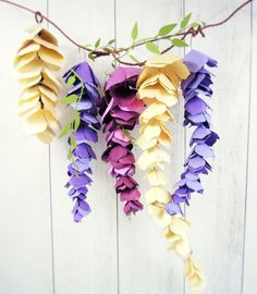 "How to make paper wisteria Most of you know that paper flowers are totally ""my thing"" 🙂  I am on a mission to attempt to create pretty much any kind of flower that exist in nature into paper flowers.  Today I'll be sharing how I came up with this paper hanging wisteria design.  Wisteria is …"