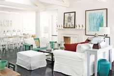 LOVE this beach space:  the little figures on the fireplace, the ottoman on the side of the coffee table, the dark floors, white walls, giant letters in the dining area, I could go on and on.