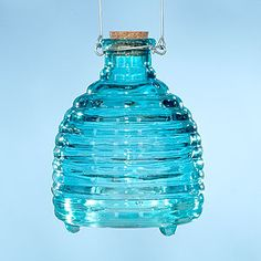 """Rid your outdoor entertaining area of pesky wasps with our Glass Wasp Catcher in Blue. Fill this pretty blue jug with sugar water or lemonade, cork the top and hang or place outside in affected area. Wasps, hornets and yellow jackets will be attracted to the sugary liquid, and once they're inside, they can't escape. The hook allows for easy hanging, while the bottom """"feet"""" allow it to sit on a table."""