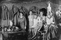 Seinälle on ripustettu valmiita takkeja Savitie 4:ssä kotiompelimossa. Kuvaan on asettunut viisi naista ja kolme tyttöä. Yksi naisista ompelee Singerillä ja yksi käsin. Tekstiili- ja vaateteollisuus työllisti erityisesti naisia, mutta kaikki työ ei tapahtunut tehtaissa, vaan monet yritykset antoivat naisille työtehtäviä, jotka he hoitivat kotona. Kuvaaja: H. Attila, 1933  VA9810:1228