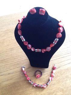 Roze ketting, armband, ring en oorbellen met zilverkleurige accenten.