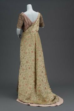 Evening dress, American, ca. 1915. Green satin brocaded w/pink, green, yellow, & blue silks & gold metal thread. Low-cut neck w/surplice line both front & back of bodice, hooked down back. Short straight sleeves, skirt longer in back forming train,open down entire left side to show gold fishnet over pink taffeta. Opening caught at center by rhinestone butterfly, left side of bodice & both sleeves made of gold fishnet w/rhinestones at intersections of netting.