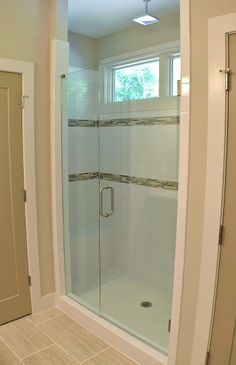 """The master bathroom shower of a Modern Prairie style home features 3""""x6"""" white subway tile with two rows of glass accent tile. The shower floor is 4""""x4"""" white tile. There is a wall shower head along with the rain shower head. Additional features include built-in bench and frameless shower enclosure. Built by Epic Development"""