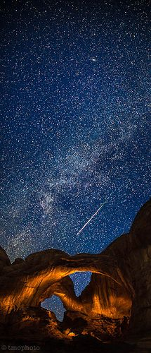 Meteor streaking over the lightpainted double arch in Arches National Park, Utah