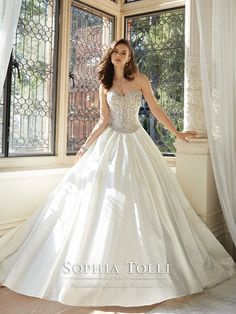 Strapless sweetheart majestic satin ball gown with ornately embroidered boned bodice, curved Basque waistline, matching embroidered appliqués on hem and chapel length train, back corset. Removable spaghetti and halter straps included. Sizes: 0 – 28 Colors: Ivory, Diamond White, White