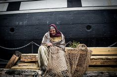 Mrs Jones works away on cutting up some fishing nets just in front of the ship, which was ...