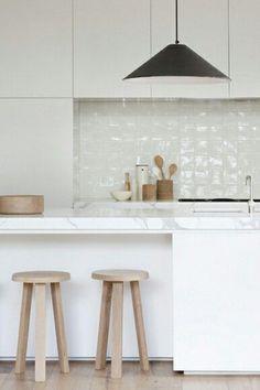 białe nowoczesne szafki kuchenne,drewniane taborety,biała glazurowana płytka na ścianie i marmurowe blaty w minimalistycznej kuchni