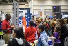 We Were There: 2018 USA Science and Engineering Festival Attendees talk with NASA staff at exhibit booths during Sneak Peek Friday at the USA Science and Engineering Festival Friday April 6 2018. At the festival NASA showcased the future of human space exploration  including the Orion spacecraft and the Space Launch System rocket.