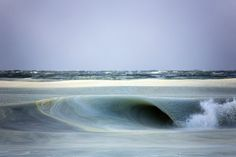 """""""Slurpee Waves"""" is a series by American photographer Jonathan Nimerfroh who is passionated by waves of the coast of Nantucket. The edge of the waves has pieces of ice, like Icee or slurpee, because of the temperature of -7 degrees. Jonathan has taken pictures of these waves, in suspension, while they were curling."""