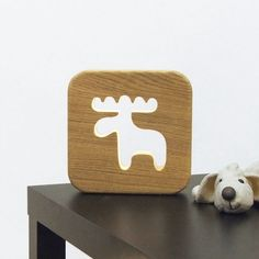 Veilleuse pour enfant,modèle caribou en bois massif  La Veilleuse est une adorable lampe naturelle qui permet d'accompagner les enfants dans leur nuit et de les rassurer grâce à la lumière douce qu'elle diffuse. Papillon, girafe, mouton ou caribou, choisissez l'animal préféré du bambin qui l'accompagnera dans son sommeil!   Corps en chene massif.  Dimensions : 20 cm x 20 cm.  Nous appliquons manuellement comme sur chacun des produits blumen une huile protectrice naturelle aux normes…