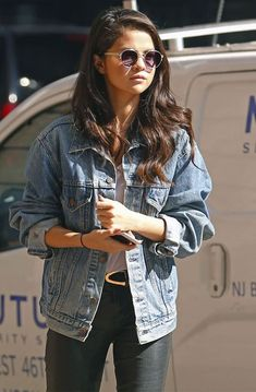 Selena looking oh-so fabulous and fierce sporting a denim jacket and round, tinted shades.
