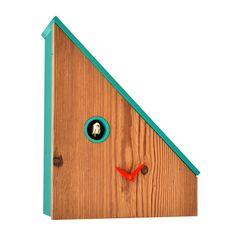 Tetto spiovente, tipico delle case del nord Europa, e l'uso di un materiale caldo, il <strong>legno di abete</strong>, sono i dettagli chiave di questo simpatico <strong>orologio a cucù</strong> che decora i nostri ambienti, sia nella modalità <strong>da appoggio</strong> sia nella disposizione <strong>a parete</strong>.  L'uccellino scandisce il nostro tempo affacciandosi dalla finestrella tonda in tinta con il tetto, completando la facciata-quadrante dell'orologio, estremamente minimal…