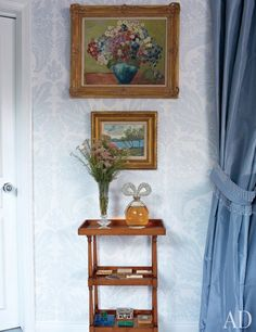 A factice of Taylor's White Diamonds perfume sparkles beneath paintings by her mother, top, and Noël Coward.