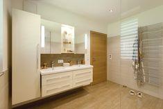 wandhängender Doppelmöbelwaschtisch mit Keramikbecken • Badmöbel mit glänzenden Lackfronten • beleuchteter Spiegelschrank • durchgehender Fliesenboden • Fußbodenheizung • Badheizkörper mit Handtuchtrockner • kontrollierte Wohnraumlüftung • Trapezförmige Einbauwanne • frei begehbare Dusche mit Thermostatarmatur, Handbrause und Regenbrause • HSH-Installatör • Holz die Sonne ins Haus • ROT-HEISS-ROT Bathroom Lighting, Bathtub, Mirror, Furniture, Home Decor, Tile Floor, Guest Toilet, Full Bath, Playing Games