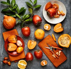 Still life of various orange colored fruits and vegetables on concrete by Trinette Reed