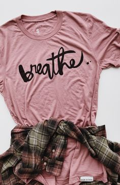 The graphic tee is always on trend. Especially in trendy blushes and rose colors, with a bold and positive message. Try pairing this Dusty Rose Breathe Tee with a pair of black denim shorts. Pull on a chunky and cozy cardigan for cooler evenings and choose your favorite summer sandals to complete the look!