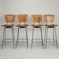 "Set of Four Arthur Umanoff Iron and Slat Wood Swivel Bar Height Stools  --  Circa 1960s set of four bar height stools designed by Arthur Umanoff. Swivel slat wood seats are curved and set on tall, narrow black iron bases with foot rests. These stools are bar height with 29.5"" height seats, but can be reduced to counter height for an additional charge. Sold and priced as a set.  --   Item:  7707  --  Retail Price:  $1695"