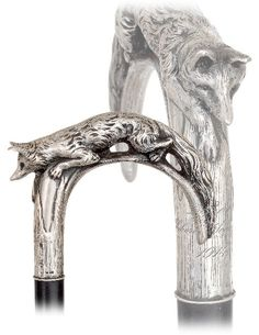 """Silver Fox Cane-Dated 1914-Large silver crook handle naturalistically modeled and finely hand chased with a crouching fox with distinguishing pointed muzzle flanked by a tiny pair of inset garnet eyes, triangular ears and long and bushy tail. The well-proportioned handle is engraved """"I. Reis, Hubertus Schiessen, 1914"""", is struck with Josef Tremesberger maker's mark beside various Viennese hallmarks and comes on a ebony shaft with a horn ferrule"""