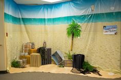 Scene setters and old luggage create the feel of an island adventure. Explore more decoration ideas at Concordia Supply!