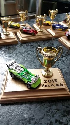 DIY BSA Pinewood Derby Cub Scout trophy. These were very easy to make and cost about $2.50 each. I bought the wood platforms at Hobby Lobby 4 for $2.99, added Hot Wheels car about $1.25 each, a plastic trophy sold 4 for $1 at the dollar store in the party section. First, I sprayed them gold with a can of Krylon Cover maxx in metallic gold $3.49 a can. After allowing them to dry for 36 hours (because that's when I had to finish them in time for the race), I positioned the car and trophy onto…