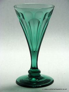Regency apple Green Wine Glass c1830 A funnel bowl with petal cuts that continue onto the stem. Slice cuts continue down onto the single cushion knop . Conical foot with polished pontil. The glass contains some inclusions and small air bubbles as one would expect.