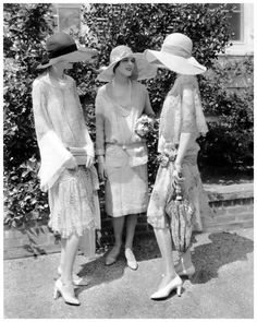 Three models talking and standing before bushes; From left to right: Alden Gay wearing a black and white chiffon dress by Madame Frances and a wide-brimmed hat; Marion Morehouse, wearing a light-colored chiffon dress by Jay-Thorpe, with a wide-brimmed hat; Miss Collier, holding a parasol, and wearing a printed chiffon and lace dress with a Tuscan straw hat
