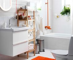 View of the bathroom. White suite and walls, wooden IKEA shelving unit and orange shower.