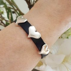 The three silver hearts on the contrasting black textured leather look great on any arm.