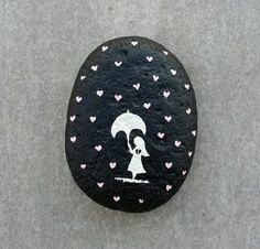 A broken-hearted little girl holding an umbrella, painted white on a smooth, black-painted stone, surrounded by raining pink hearts.