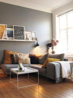 Grijs als basis kleur gemengd met warme kleuren. De lijsten op een plank aan de muur maakt het af.