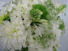Brides bouquet of white dahlia, tuberose, trick dianthus, freesia and Queen Anne's lace.