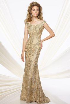 Montage by Mon Cheri. Tip-of-the-shoulder metallic lace and tulle fit-and-flare gown with slight cap sleeves. Bateau neckline, scalloped hem and sweep train. Matching shawl included.