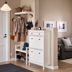 A small hallway with a white shoe cabinet and a seating bench with shelves for shoes.