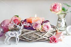 Hirschfigur vor Flechtkorb mit Rosenblüten, Kerzen und Weihnachtskugeln