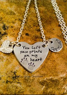 A pet memorial necklace beautifully quoted on a heart pendant with the words You left paw prints on my heart. Two adorable paw prints also