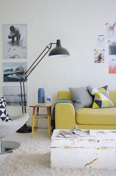 sofá amarelo na decoração da sala de estar com almofadas cinza e luaminária de chão preta. banco como mesa lateral