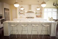 An in-kitchen eating area - perfect for kids and family or for entertaining - is a key feature in this open-plan kitchen. The symmetry, along with the all-white cabinetry and tile backsplash, make the room feel large, clean and organized. Modern-style hanging globes give the space an industrial look while providing plenty of lighting.