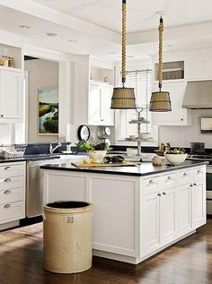 This kitchen uses an antique crock as a trash or compost receptacle. The interior is painted black, which references the same lines and tones in the hanging lamps.