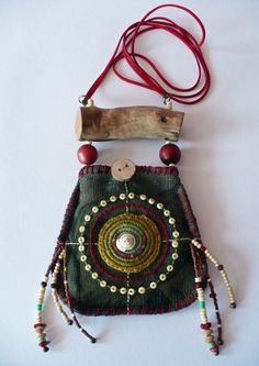 This pouch bag has strings of suede, the wood, is Norwegian driftwood which is light and smooth. on the wood hangs the bag its tapestry fabric in green color and is lined with cotton fabric. height 13cm, breedte14cm. There is a crochet spiral of wool on embroidered with a shell in the middle. The large beads are made of wood. The small beads of bone, wood, glass, metal and coral.  This jewelry is made with care and love and uniek1