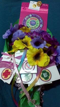 We created small bouquets to present the girls their badges at the end of the year party.  The badges they earned are dangling at the bottom, the journey award and membership pin are at the top.  The other pin is Our Lady of Guadalupe, a religious award.