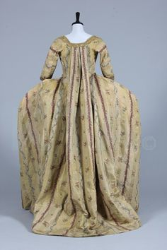Back view robe à la Francaise, Italy or Spain, c. 1770. Gold brocaded striped silk, woven with puce and silver bands within the textured cloth of gold stripes, pretty floral sprigs and trails, edged and trimmed with scalloped gold bobbin lace.