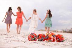 Bridesmaids walking on the beach.