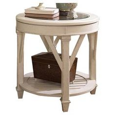Handcrafted pine end table in antiqued linen with an open bottom shelf.    Product: End table       Construction Material: Deluxe pine solids, birch veneers, and glass         Color: Antique linen    Features:    Dentil molding  Bead board backs  Cantilevered moldings  Band saw cabriole legs  Bottom shelf  Glass top        Dimensions: 26 H x 26 Diameter