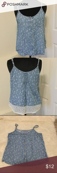 """👗5 for $30 SALE!👗Blue Denim Tank Top White flowers all over a blue denim tank with adjustable straps. Pocket in front and white lace in back at hem. 60% lyocell and 40% viscose. Measurements: pit to pit is 18 1/2"""" and from top of strap down is 23"""". Shows normal signs of wear but no rips, stains or tears. So cute!!! Maurices Tops Tank Tops"""