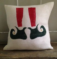 We love this cute Elf shoe design! The Perfect touch for Christmas decorating. Hand painted green, red, and gold on white burlap. Pillow #TPDholiday